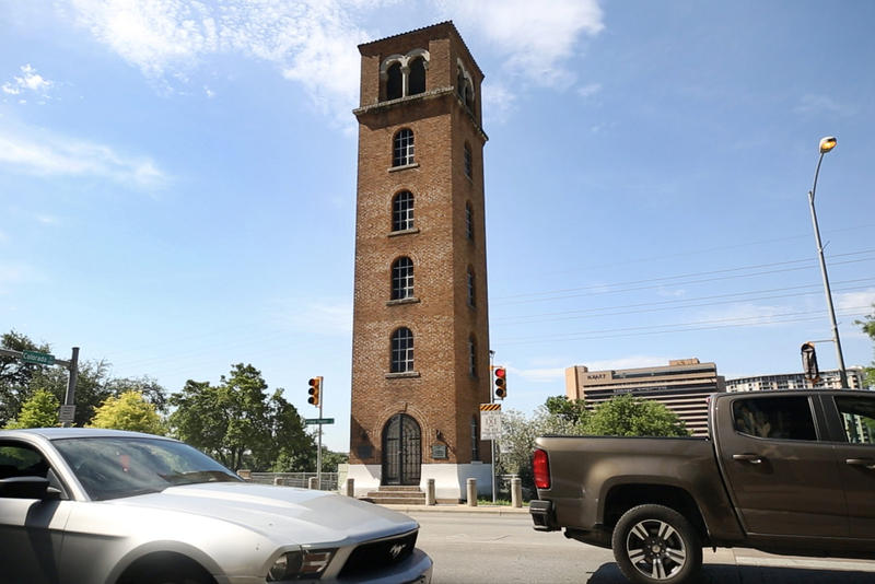 A red brick tower stands on Cesar Chavez, overlooking Lady Bird Lake.