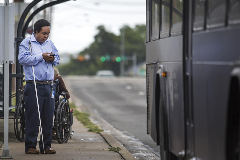 Martin Kareithi, program manager of accessible services at Capital Metro, uses a pilot app for blind and low-vision riders to navigate to a bus stop.