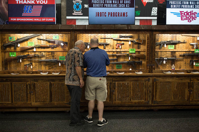 Attendees check out guns on display at the National Rifle Association's annual meeting in Dallas last month.