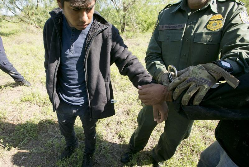 A Border Patrol agent handuffs two Mexican nationals near the border in October.