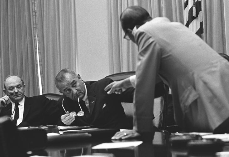 General Earle Wheeler leaning forward, speaking to President Lyndon B. Johnson and gesturing as Secretary of State Dean Rusk (left) looks on.