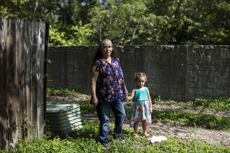 Noemi Everett stands with her granddaughter Anaya near a flood-retention wall along Walnut Creek. The wall was built to protect the Las Cimas neighborhood from flooding, but a new floodplains map shows it might not be enough.