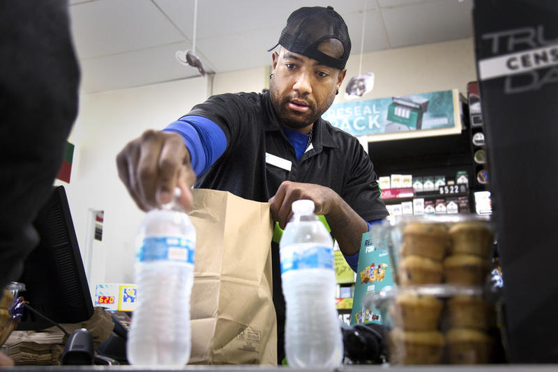 Will Jones sells water to shoppers at 7-Eleven in West Campus after the City of Austin issued a citywide boil-water notice due to high levels of debris, silt and mud in the water supply.