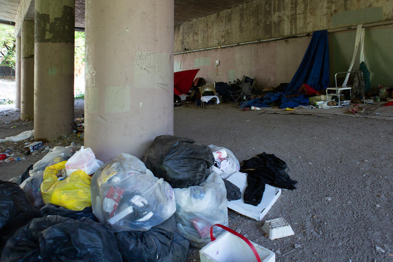An encampment under the Eigth Street bridge, a short walk down from the Austin Police Department headquarters. Police hand out tickets for sitting or lying on sidewalks, camping or panhandling, but the city says it's revisiting those laws this year.