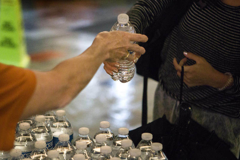Volunteers distribute bottled water to UT students on campus Wednesday.
