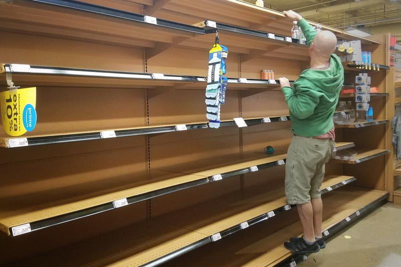 A man reaches for a water bottle in a mostly empty bottled water aisle at Whole Foods on Sixth Street and Lamar Boulevard.