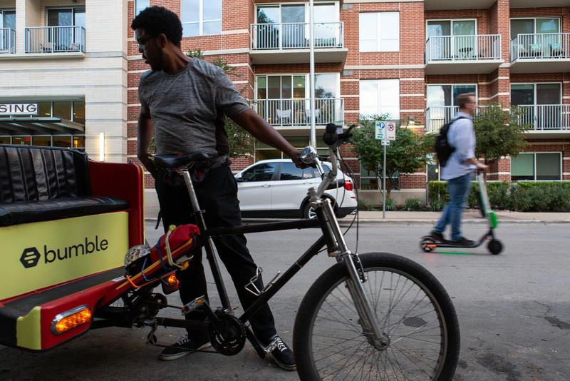 Bernard Love, a driver for Austin Pedicab, waits for customers on Rainey Street.