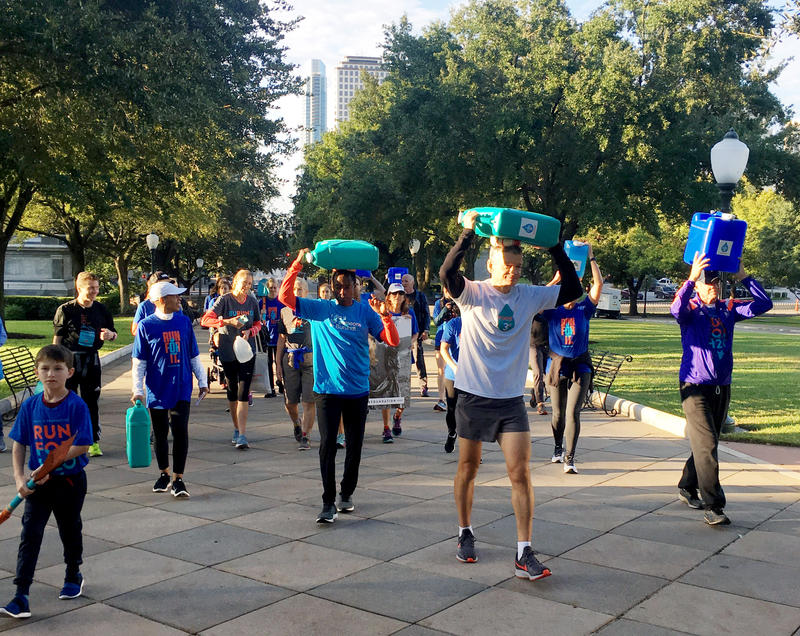 A group walks from Auditorium Shores to the state Capitol on Friday, simulating the journey many Burundians take to get water.