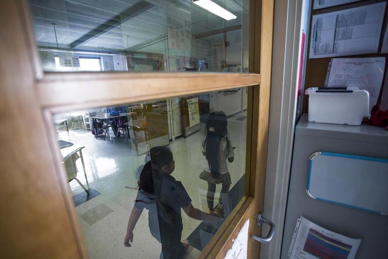 Children walk down a hallway at a school.