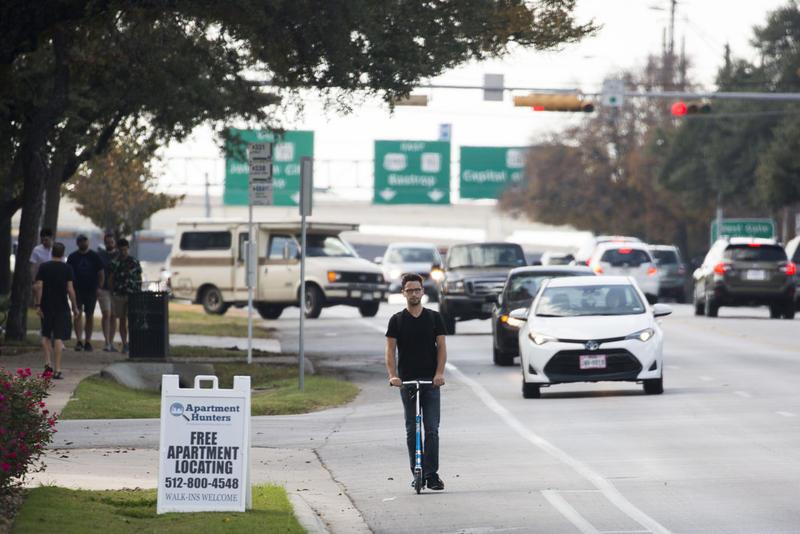 A man rides a scooter down South Lamar.