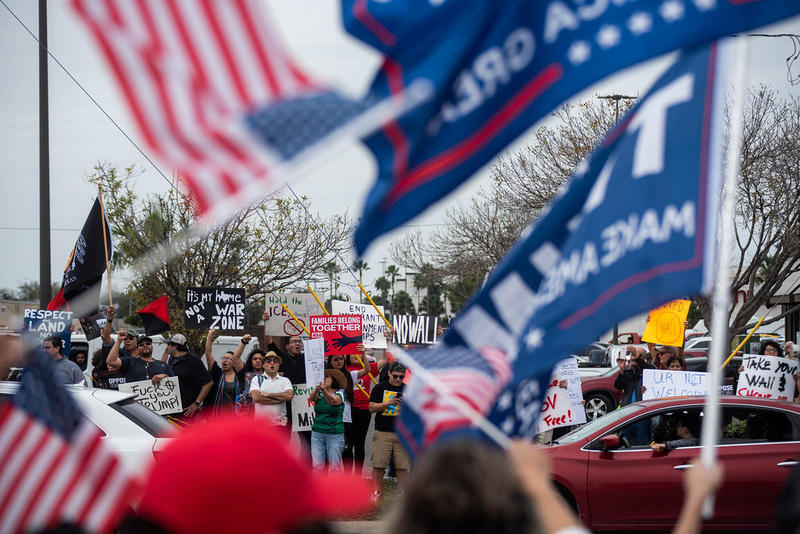 Supporters and opponents of President Trump's border wall stand on opposite sides of a street in McAllen, Texas, on Thursday. Trump visited the town to drum up support for construction of his long-promised wall.