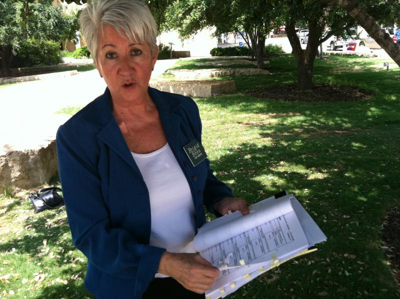 Mayoral candidate Brigid Shea holds a list of contributors to Lee Leffingwell's campaign.