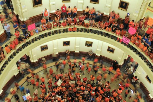 Hundreds of abortion rights demonstrators encircled a group of anti-abortion demonstrators in the Capitol Rotunda, while even more demonstrators from either side watched and cheered from above.