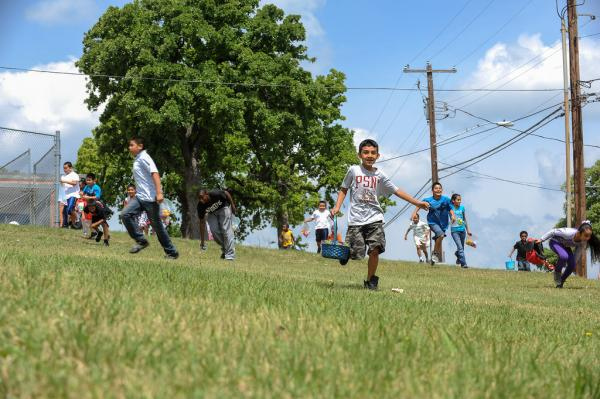 Kids scramble to as the egg hunt kicks off during the Bad Boyz's Easter party in East Austin.
