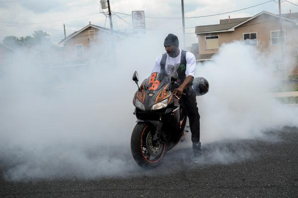 "Demetrius Miles does a ""burn out"" after the children have left his motorcycle club's Easter event."