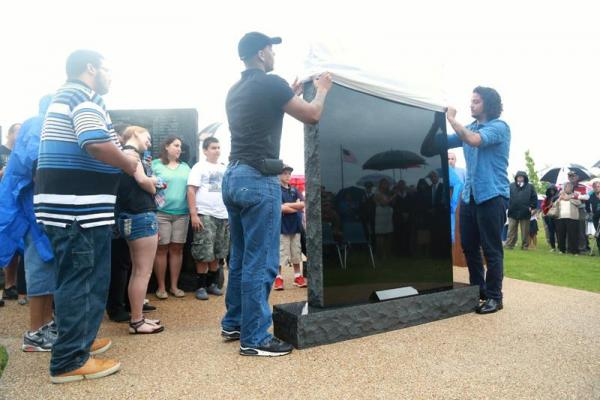 Family members of three Central Texas soldiers who died in combat last year help unveil a memorial dedicated to those soldiers at the Central Texas State Veterans Cemetery on May 26, 2014.
