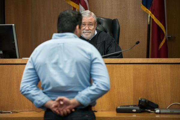 Judge Herb Evans, filling in for Judge Mike Denton, speaks to a veteran at the Travis County veterans court on May 15, 2014.