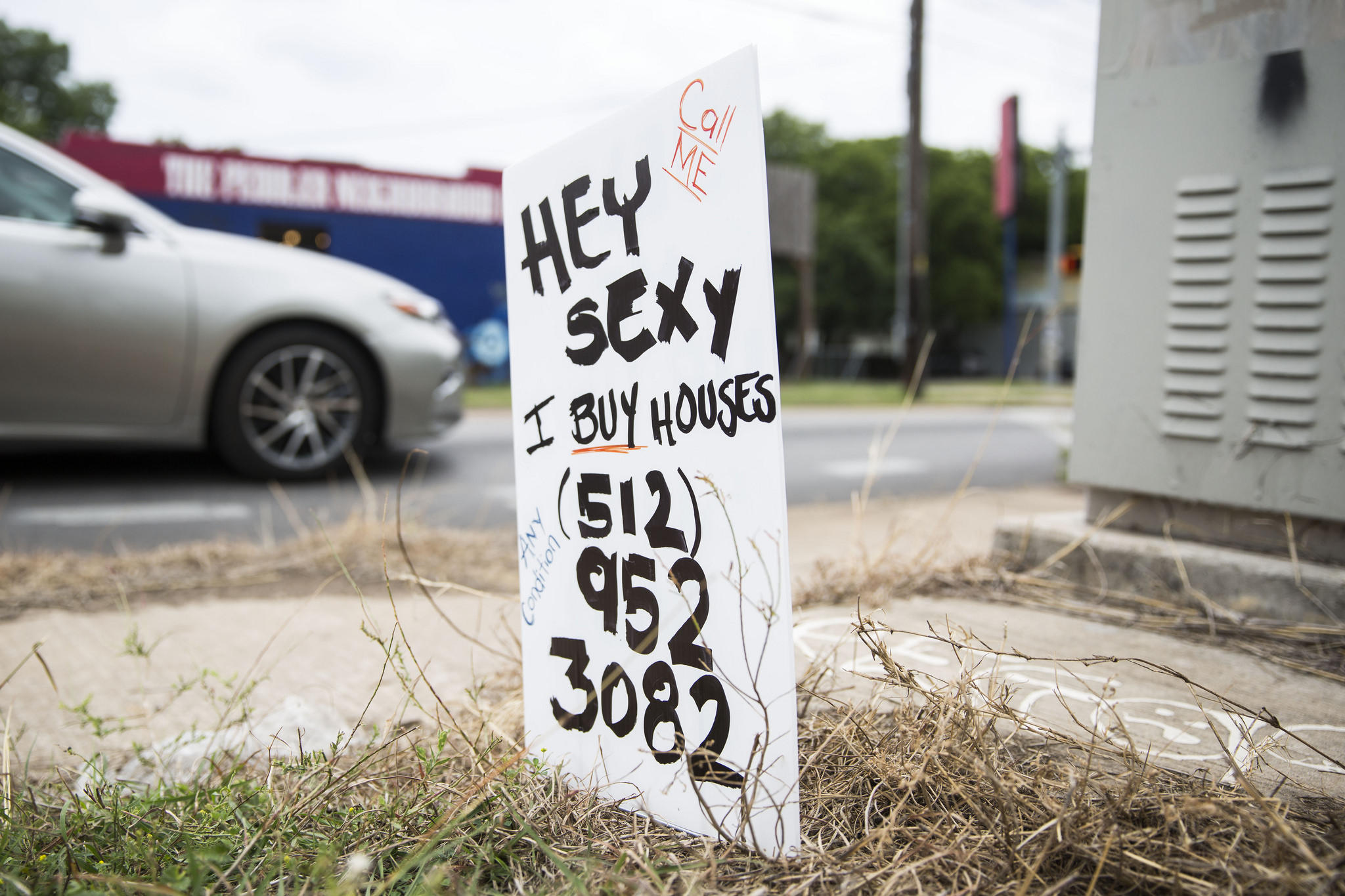 what s up with those handmade we buy houses signs around austin kut