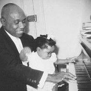 Luis Russell with daughter Catherine at the piano