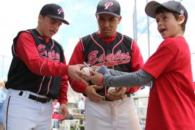 Kyle Manuppella, left, and Jorge Quinonez sign a game ball for Slater Podgorny, whose dad, Greg, who was diagnosed with ALS.