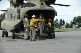 Colorado Army National Guardsmen and civil rescue personnel unload evacuated residents from Colorado flood zones at the Boulder Municipal Airport in Boulder, Colo., Sept. 13, 2013.