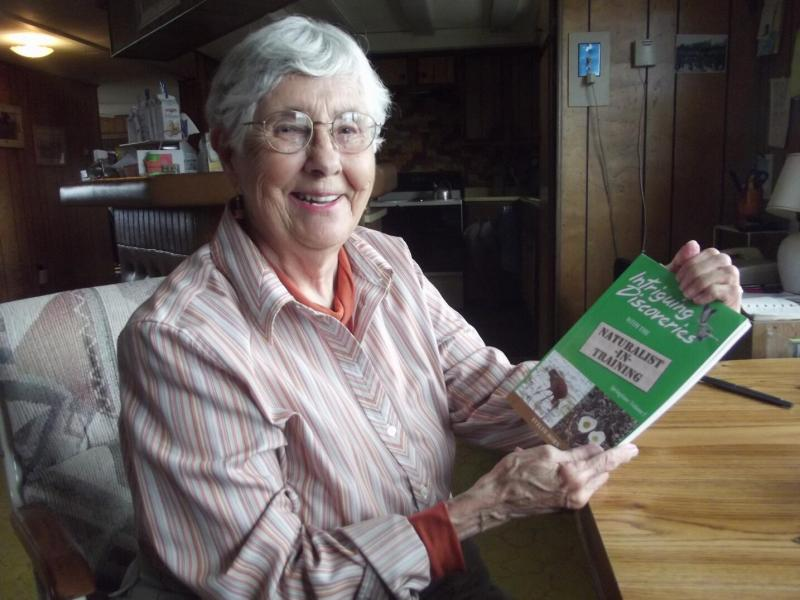 "Evy and one of her own books, ""Intriguing Discoveries with the Naturalist in Training."""