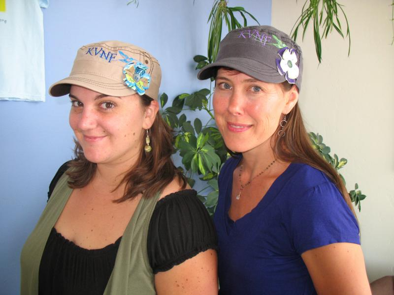Limited Edition fatigue style hat with fanciful KVNF hummingbird logo and custom Elisabethan flower. (Modeled by KVNF Underwriting Director Amber McDaniels and Interim General Manager, Christy Eller)ty Eller