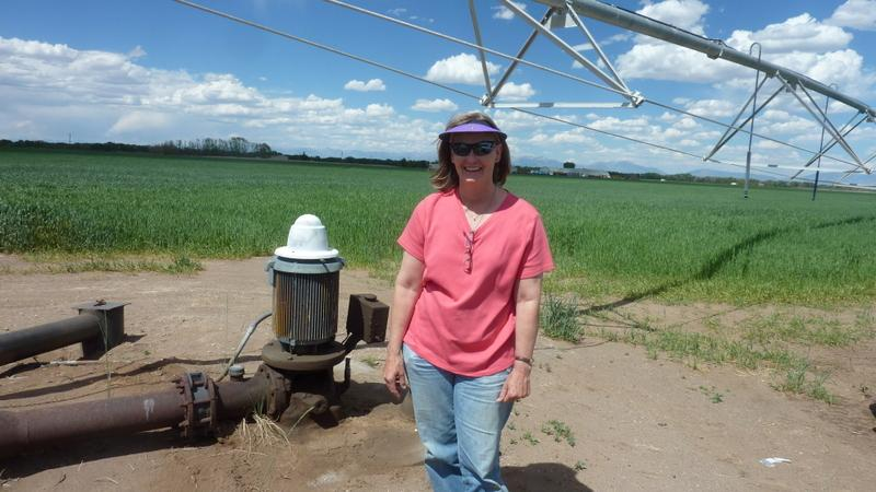 Karla Shriver standing by one of the many pivot sprinkler systems that she uses to irrigate her approximately 1,000 acres of potatoes, small grains, and hay on her farm, just north of Alamosa, Colorado