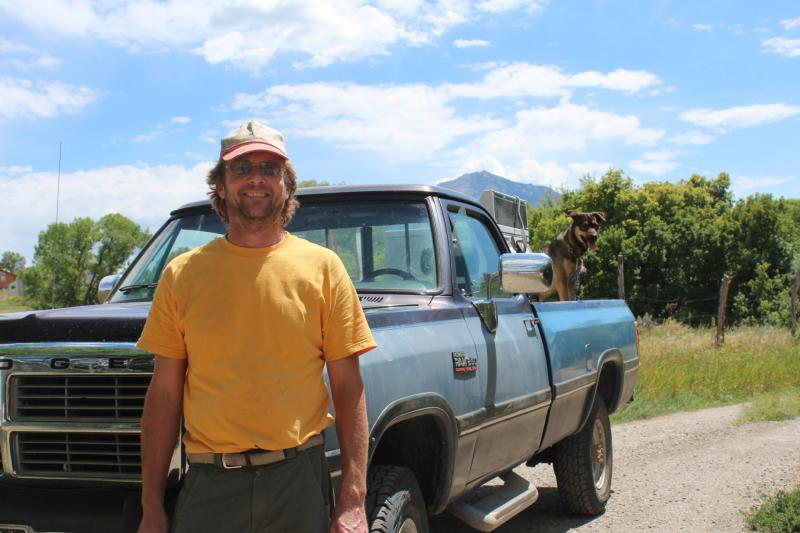 Kael Frank in front of his home (and beautiful truck) in Paonia