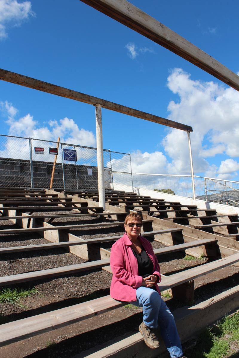 Susan Long, seated on one of the aging grandstands benches