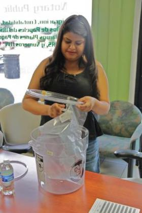 Byanka Santoyo demonstrates how residents capture air quality samples with a bucket.