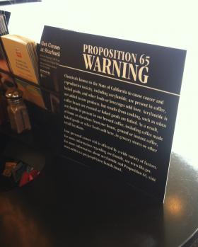A Proposition 65 mandated warning sign sits inside a Starbucks in Fresno, CA.
