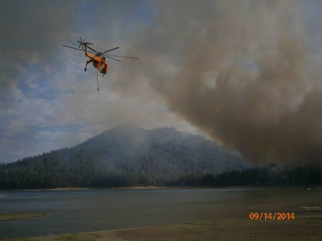 A helicopter picks up water from Bass Lake to drop on the Courtney Fire on Sunday September 14th.
