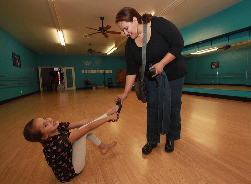 Emily Gorospe, at the dance studio in Delano, jokes with her mother, Valerie. Emily was forced to leave dance lessons after she was diagnosed with valley fever.