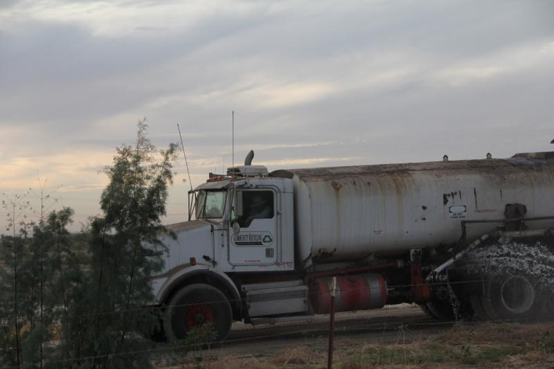 A Community Recycling truck sprays water on ground along North Wheeler Ridge Road near Arvin.