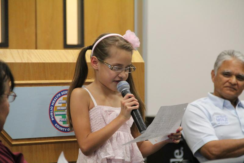 7-year-old Emily Gorospe reads from a handwritten note describing how valley fever has changed her life, at a town hall event in Bakersfield last year hosted by state Sen. Michael Rubio.