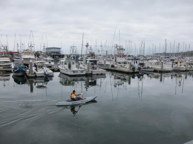 Kayaker sets out at fishing docks of Half Moon Bay, CA.
