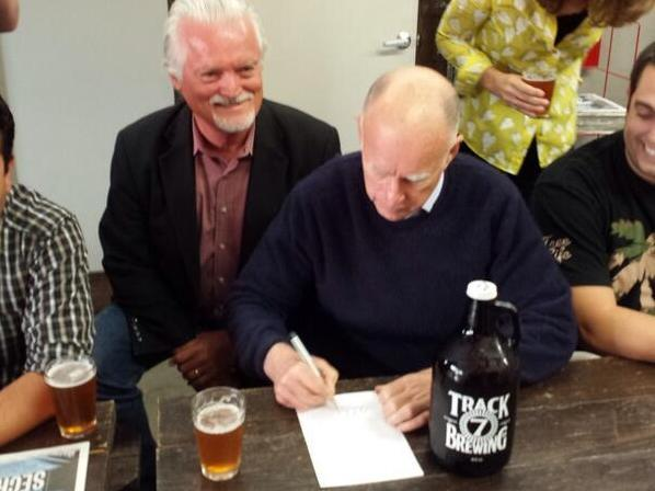 California Gov. Jerry Brown signs a measure allowing craft breweries to refill growlers at Sacramento's Track 7 Brewing Company in October.