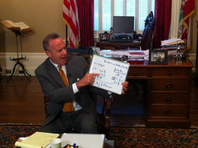 Senate President pro Tem Darrell Steinberg (D-Sacramento) holds up a white board full of budget numbers as he meets with reporters at the state Capitol Wednesday.