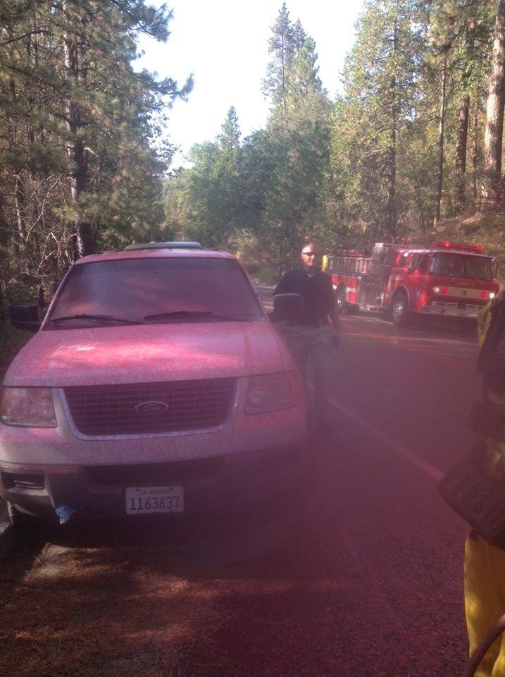 Pink fire retardent dropped from one of the nine air tankers battling the Courtney Fire covers vehicles and first responders near Bass Lake.