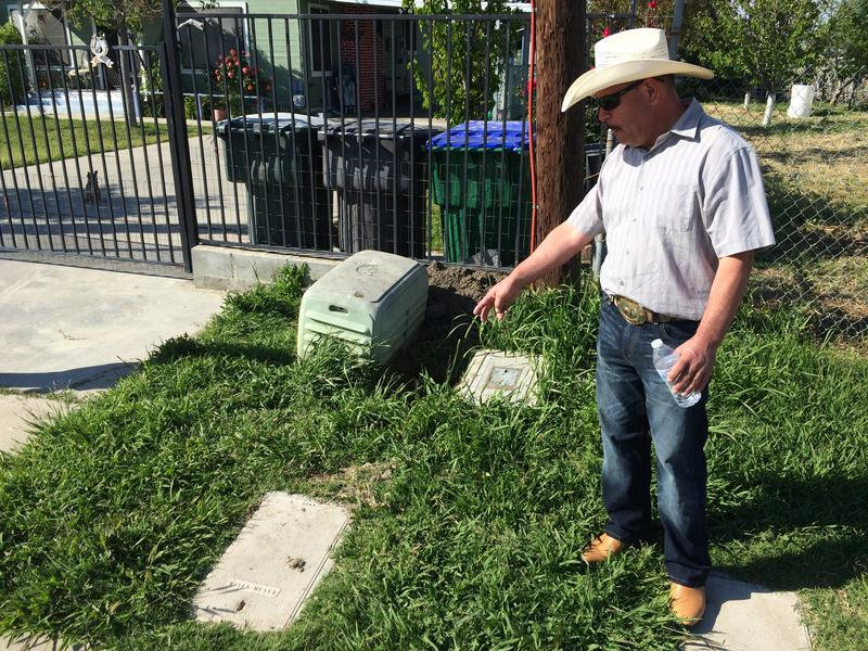 Javier Medina points to a hole where a water meter is being installed--one of the final steps required for Matheny Tract to begin receiving clean drinking water