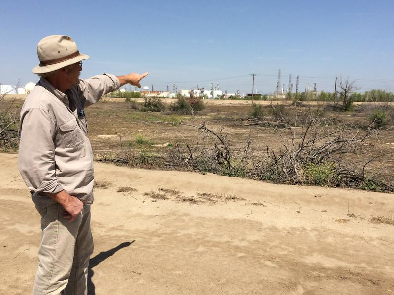 Air quality advocate Tom Frantz points to an idle oil refinery near the Rosedale Highway just west of downtown Bakersfield.