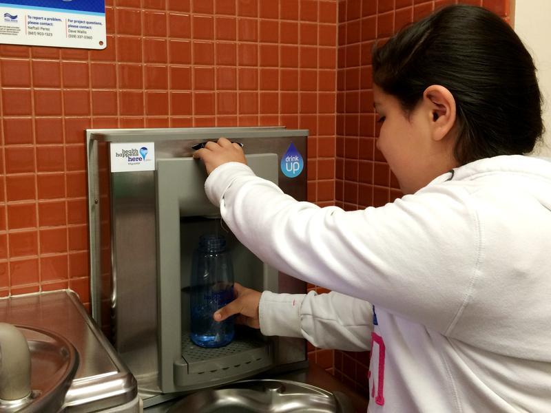 A sixth-grader at El Camino Real Elementary School in Arvin uses a water bottle filling station equipped with an industrial water filter, installed because Arvin's public water is contaminated with arsenic.