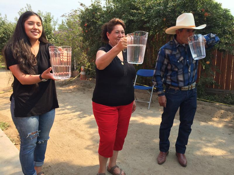 Tania, Guillermina and Leonicio Ramirez hold up the first running water they've had at their home in over three years.