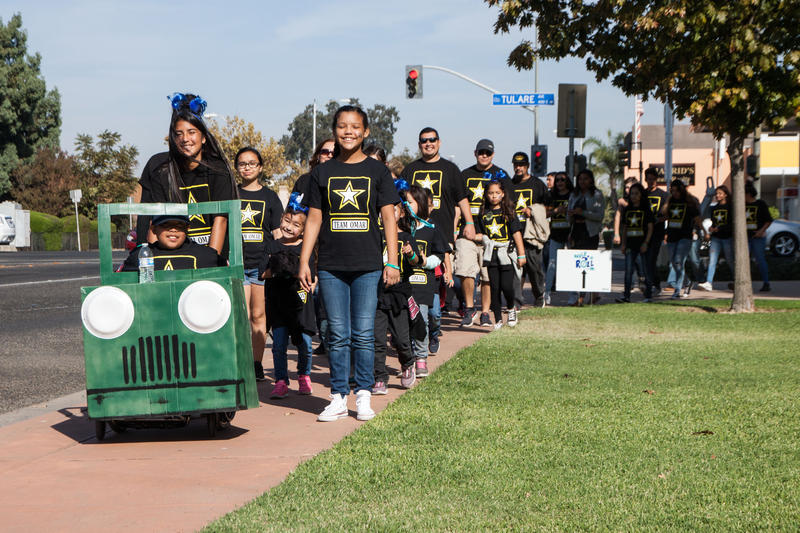 Friends and relatives walk in support of 10-year-old Omar Macias, far left, at the annual Walk for Spina Bifida in Tulare.