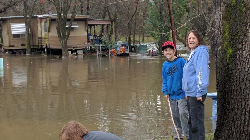 Selma Metzger and her grandson look at their nearly flooded home
