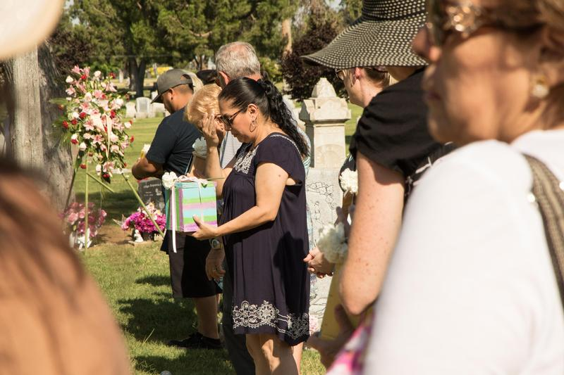 """Attendees pass each urn around a """"Circle of Love"""" on its way to the garden."""
