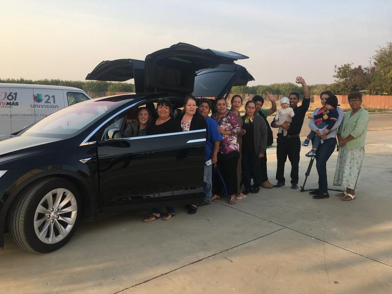 Residents of Cantua Creek and El Porvenir and representatives of the Leadership Counsel for Justice and Accountability stand with their new Tesla Model X, to be used for a community ride sharing program.