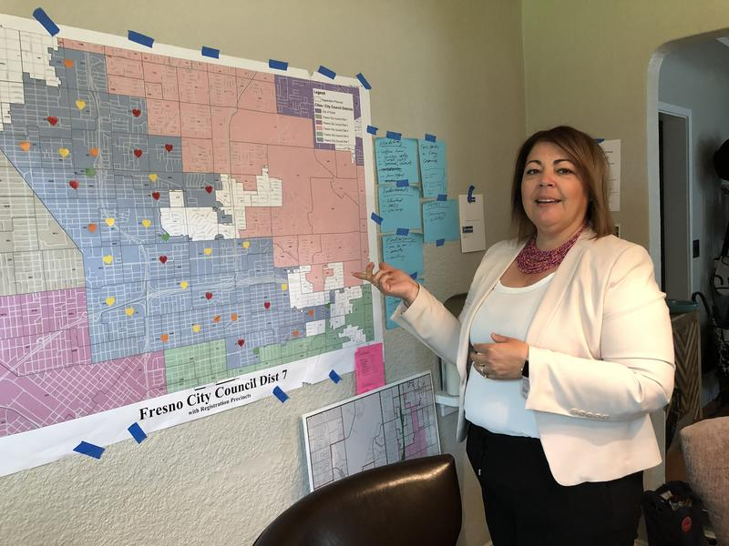 City council candidate Veva Islas points out the shape of District 7, highlighted in blue on a map taped to her kitchen wall.