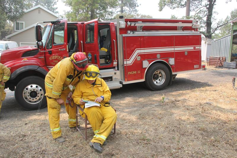 Volunteer fire fighters from Mariposa County (Engine 22) go over plans for a structure protection mission near Lush Meadows.